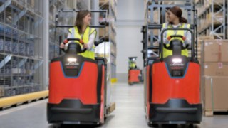 Two employees drive in the warehouse with order pickers of the N20 series from Linde Material Handling.
