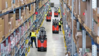 Employees work with order pickers of the new N20 series from Linde Material Handling in a warehouse.
