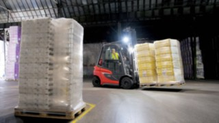 Linde forklift truck transporting goods in a dark hall with light