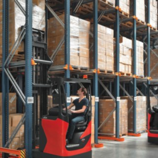 Two Linde reach trucks in use on a rack.