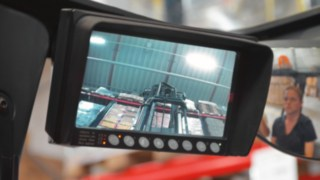 The camera system mounted on the mast of Linde reach trucks helps the operator safely position the load in the rack.