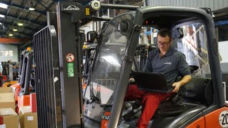 Technician with laptop inspection a truck for the preparation as an approved truck
