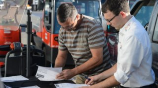 A Linde employee goes through the handover report for rental trucks with Johannes Kratzel
