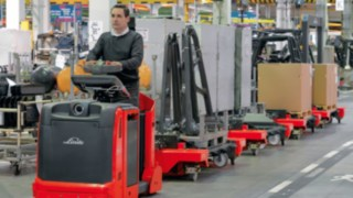 Operators on Linde logistics trains in a production hall