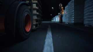Short video showing forklift truck and warehouse worker crossing paths in a dark warehouse environment